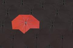 Parapluie rouge et entouré par un parapluie noir Photo libre de droits
