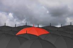 Parapluie rouge et entouré par un parapluie noir Image stock