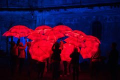 Parapluie rouge illuminé par les lampes menées pendant la nuit Photographie stock libre de droits