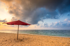 Parapluie rouge sur une plage Photos stock