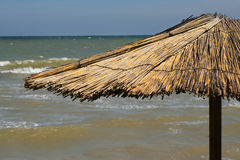 Parapluie sur la plage avec la mer derrière Image stock