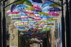 Parapluies colorés accrochant dans l'allée orange célèbre de rue images stock