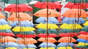 Parapluies colorés accrochant dans le plein vol Images stock