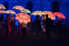 Parapluies colorés illuminés par les lampes menées pendant la nuit Image libre de droits