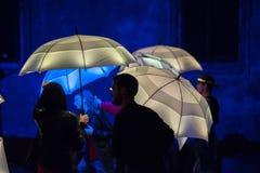 Parapluies colorés illuminés par les lampes menées pendant la nuit Photo stock