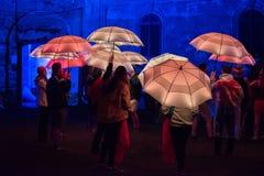 Parapluies colorés illuminés par les lampes menées pendant la nuit Photographie stock
