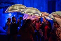 Parapluies colorés illuminés par les lampes menées pendant la nuit Photos stock