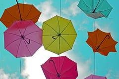 Parapluies colorés sur un fond des nuages Vue du fond au ciel photos stock