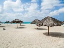 Parapluies couverts de chaume sur la plage d'Aruba Photographie stock