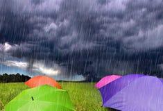 Parapluies de couleur en nuages de tempête pluvieux Images stock