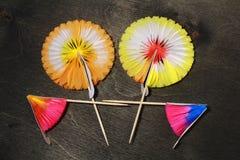 parapluies de papier pour des cocktails sur le noir Photographie stock libre de droits