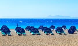 Parapluies de plage colorés avec le caillou et l'île de chaises de plate-forme dans la distance Image stock