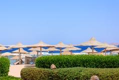 Parapluies de plage couverts de chaume à une station de vacances tropicale Photos stock