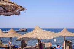 Parapluies de plage couverts de chaume à une station de vacances tropicale Images libres de droits