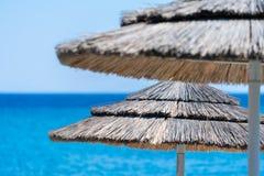 Parapluies de plage faits de paille sur une plage photographie stock libre de droits