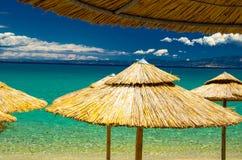 Parapluies de plage jaunes de paille et eau azurée, Pefkohori, Grèce photographie stock