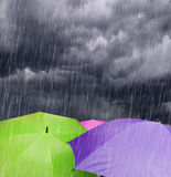 Parapluies en nuages de tempête pluvieux Photo stock