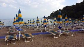 Parapluies et canapés du soleil sur la plage images stock