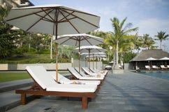 Parapluies et canapés par la piscine Photographie stock