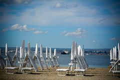 Parapluies et chaises fermés blancs de sable sur la plage Photographie stock