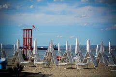 Parapluies et chaises fermés blancs de sable sur la plage et une Floride rouge Photographie stock