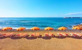 Parapluies et chaises longues sur une plage Images stock