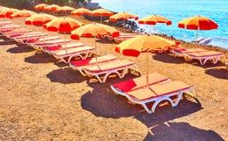 Parapluies et chaises longues sur une plage de mer Images stock