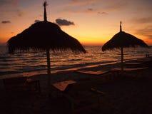 Parapluies et coucher du soleil sur la plage Images libres de droits