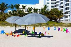 Parapluies et jouets pour enfants de plage sur le sable Images stock