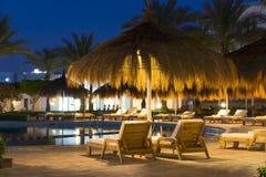 Parapluies et lits pliants de paille par la piscine dans le Sharm el Sheikh Photo stock