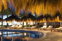Parapluies et lits pliants de paille par la piscine dans le Sharm el Sheikh Image libre de droits