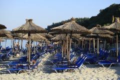 Parapluies et lits pliants de plage de paille sur la plage image stock
