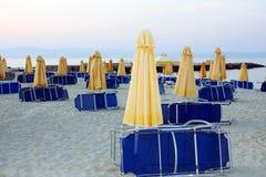 Parapluies et sunbeds sur une plage abandonnée Image stock