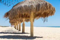 Parapluies faits main de paille sur une mer Photos libres de droits