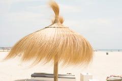 Paraply för skugga på stranden i blåsig dag arkivbild