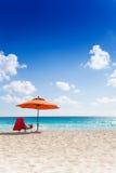 Paraply och stol på stranden arkivfoton