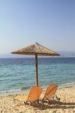 Paraply och stolar på stranden Royaltyfri Bild