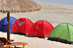 Paraply och tent på sjösida Arkivbilder