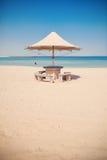 Paraply på en tom tropisk strand Arkivfoton