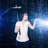 paraply under kvinna Flickainnehavhand ut som trycker på regndropparna Arkivfoto