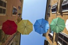 Paraplyer av olika färger över gatan med blå himmel som bakgrund Arkivfoto