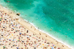 paraplyer för strandsunbedsturister Arkivbilder