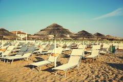Paraplyer och chaisen är slö på stranden av Rimini i Italien Royaltyfri Fotografi