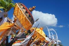 Paraplyer och flaggor för traditionell Balinese ceremoniella på stranden Arkivbild