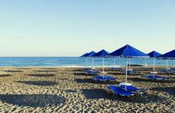 Paraplyer och solstolar på stranden Arkivfoton