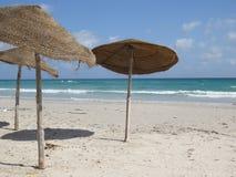 Paraplyer på den sandiga stranden i Tunisien royaltyfria bilder
