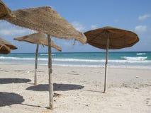 Paraplyer på den sandiga stranden i Tunisien arkivfoton