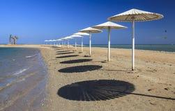 Paraplyer på stranden mot den blåa himlen Royaltyfria Bilder
