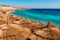 Paraplyer på stranden i korallrev Royaltyfri Foto