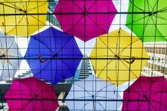 Paraplyer som beskyddar folk från regnet i världsfyrkant Arkivbilder